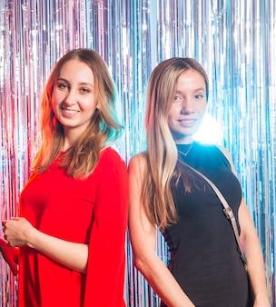 Portret dwa atrakcyjnej szczęśliwej kobiety ściska i patrzeje kamerę odizolowywającą nad srebrem w sukniach wieczorowych barwił błyszczącego tło. koncepcja przyjęcie urodzinowe, wakacje i klub nocny.