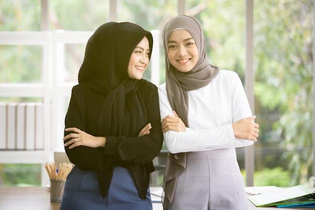 Portret dwa azjatyckiej muzułmańskiej kobiety opowiada wpólnie w biurze