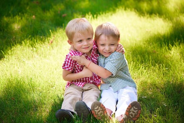 Portret dwa chłopiec obejmuje i śmia się outdoors