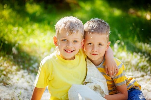 Portret dwa dzieciaki ma zabawę outdoors. dzieci odpoczywają w