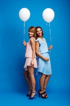 Portret dwa dziewczyny odpoczywa przy przyjęciem nad błękit ścianą