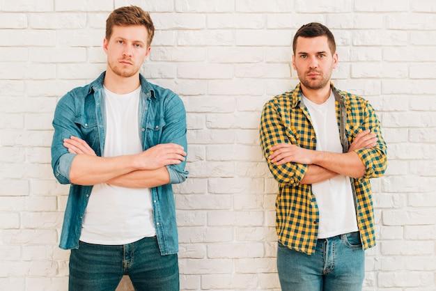 Portret dwa młodego męskiego przyjaciela z ich rękami krzyżował patrzeć kamerę