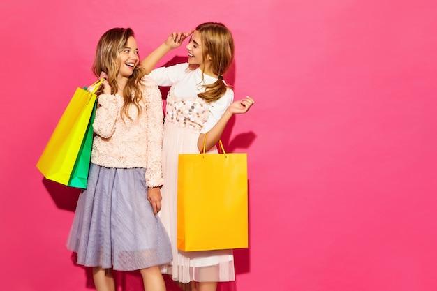 Portret dwa młodej eleganckiej uśmiechniętej blond kobiety trzyma torba na zakupy. kobiety ubrane w letnie ubrania hipster. pozytywni modele pozuje nad menchii ścianą