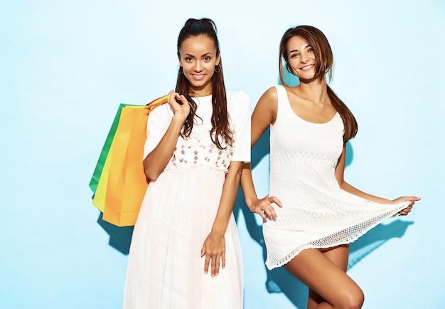 Portret dwa młodej eleganckiej uśmiechniętej brunetki kobiety trzyma torba na zakupy. kobiety ubrane w letnie ubrania hipster. pozytywni modele pozuje nad błękit ścianą