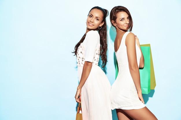 Portret dwa młodej seksownej eleganckiej uśmiechniętej brunetki kobiety trzyma torba na zakupy. gorące kobiety ubrane w letnie ubrania hipster. pozytywni modele pozuje nad błękit ścianą