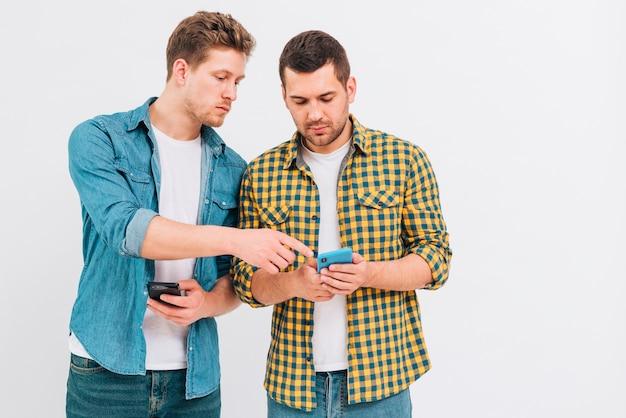 Portret dwa przyjaciela patrzeje telefon komórkowego przeciw białemu tłu