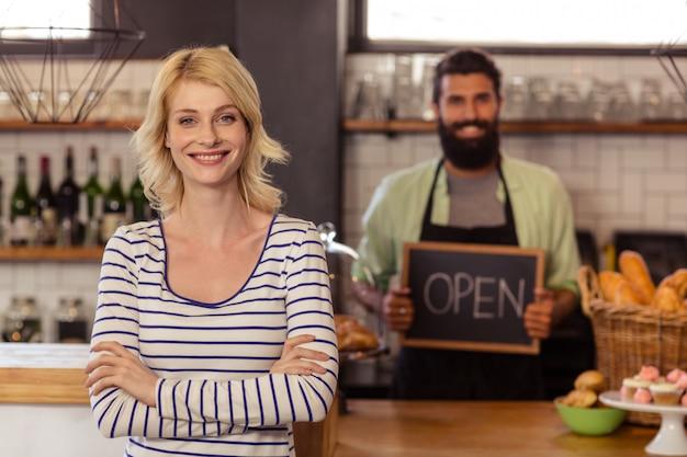 Portret dwa przypadkowego kelnera trzyma deskę pisać otwarty