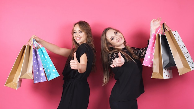 Portret dwa szczęśliwej dziewczyny po robić zakupy pozować dla kamery na odosobnionym tle