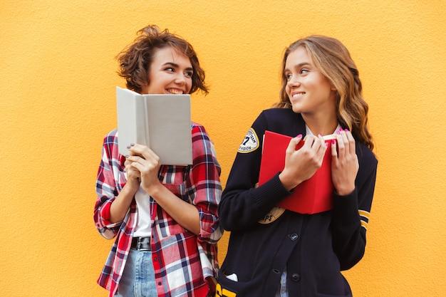 Portret dwa szczęśliwej ładnej nastoletniej dziewczyny z książkami