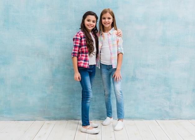 Portret dwa uśmiechniętego żeńskiego przyjaciela pozuje przed błękitną ścianą