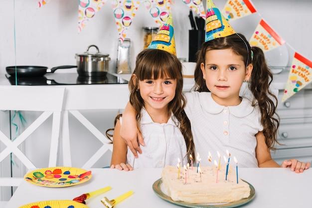 Portret dwa uśmiechniętej dziewczyny z partyjnymi kapeluszami na kierowniczej pozyci za urodzinowym tortem