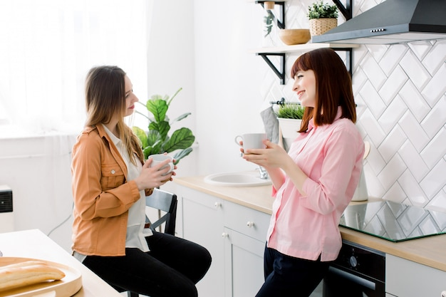 Portret dwa uśmiechniętej kobiety trzyma filiżanki kawy w domu w kuchni
