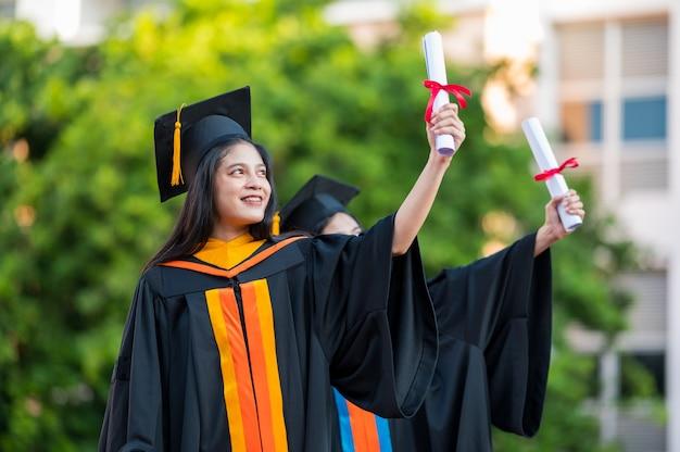 Portret dwie absolwentki, absolwentki uniwersytetu posiadające dyplom i są szczęśliwe