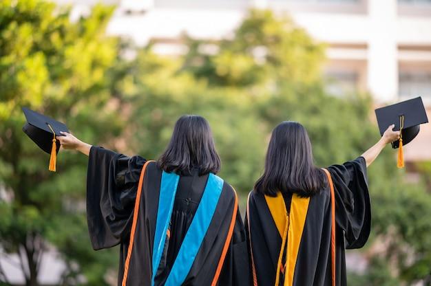 Portret dwie absolwentki, absolwentki uniwersytetu, radośnie trzymające czapki do przodu.