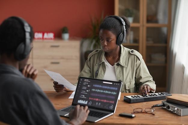 Portret dwóch afroamerykanów komponujących muzykę razem siedząc przy biurku w domowym studio nagrań, kopia przestrzeń