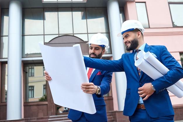 Portret dwóch architektów pracujących razem poprzez plan budowy