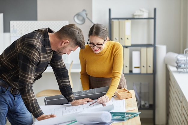 Portret dwóch architektów współpracujących przy projektach stojąc przy biurku i pracując razem w biurze,