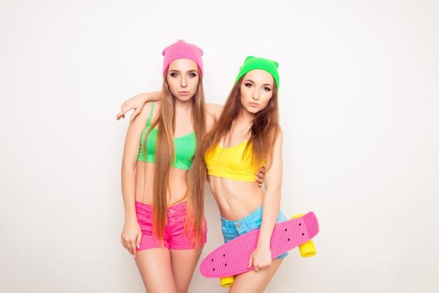 Portret dwóch całkiem młodych dziewcząt gospodarstwa deskorolka