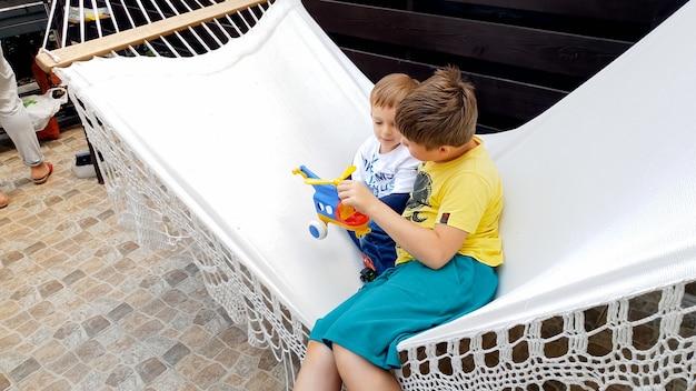 Portret dwóch chłopców leżących na hamaku na podwórku domu