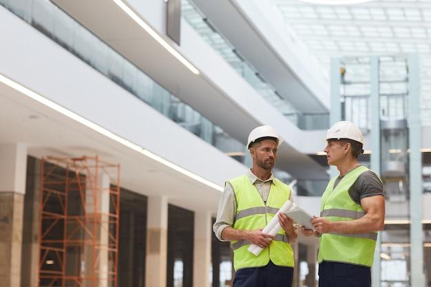 Portret dwóch dojrzałych budowniczych rozmawiających o pracy stojąc na budowie,