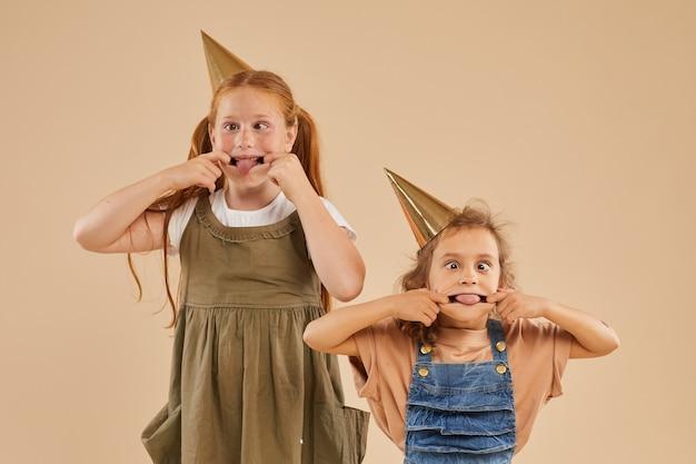 Portret dwóch dziewczyn robią śmieszne miny i grymasują podczas pozowania na beżu