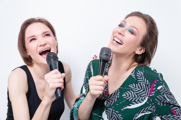 Portret dwóch dziewczyn z mikrofonami w rękach. koncepcja karaoke. różne środki przekazu