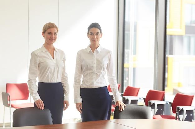 Portret dwóch eleganckich kobiet biznesu ubranych w czarno-białe stojących w pustej sali konferencyjnej