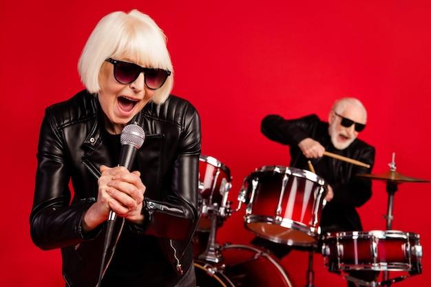 Portret dwóch emerytów emeryt emeryt ludzie kobieta śpiewać skład solo człowiek grać bęben podudzia cieszyć się wypoczynek klub nocny impreza nosić skóra na białym tle nad jasnym połyskiem kolor tła