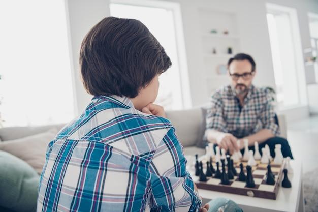 Portret dwóch fajnych, wykwalifikowanych skoncentrowanych, skoncentrowanych i poważnych facetów, tata i syn w wieku przedszkolnym siedzących na sofie i grających w szachy poruszające się pionki w jasnobiałym nowoczesnym wnętrzu salonu