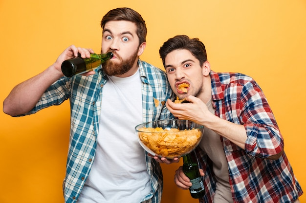 Portret dwóch głodnych młodych mężczyzn pije piwo
