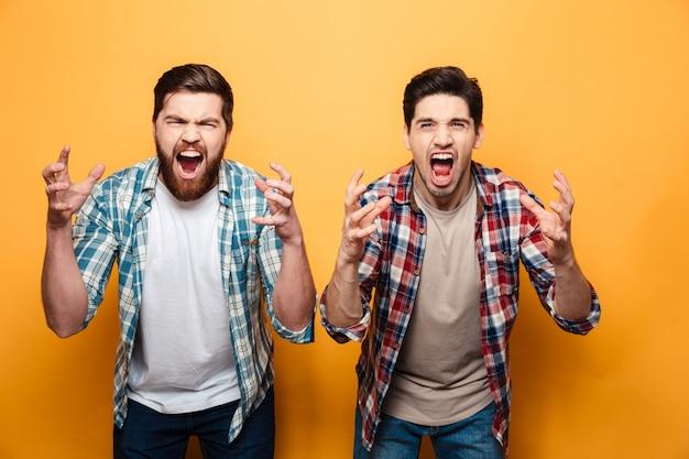 Portret dwóch gniewnych młodych mężczyzn krzyczących głośno