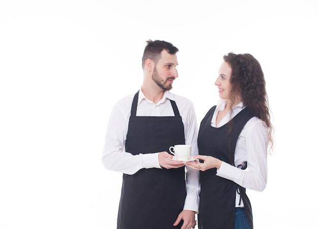 Portret dwóch kelnerów na białym tle. para pracuje w kawiarni