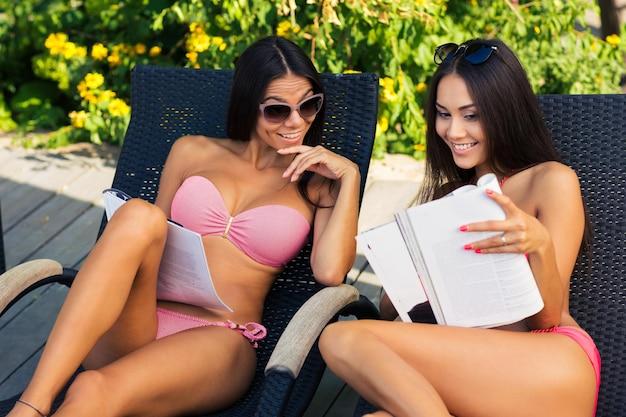 Portret dwóch kobiet czytających czasopismo na leżaku na świeżym powietrzu