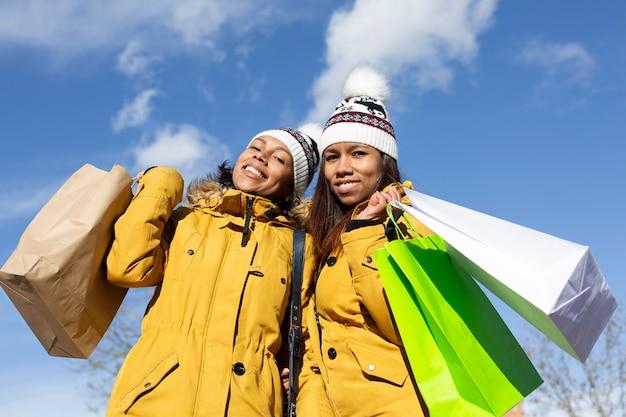 Portret dwóch kobiet łacińskiej z ich torby na zakupy na zewnątrz. niebieskie niebo. miejsce na tekst.