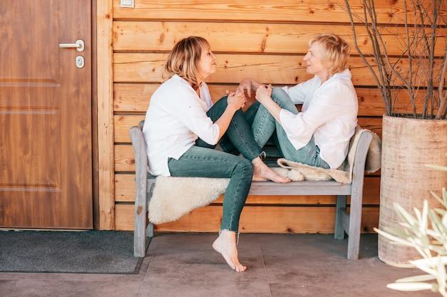 Portret dwóch kobiet na drewnianym tle siedzących naprzeciwko siebie spędzających razem wolny czas