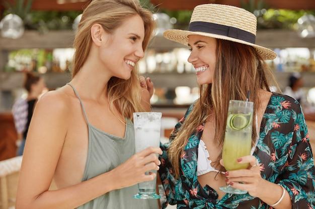 Portret dwóch kobiet spotykających się w kawiarni na świeżym powietrzu, brzęk szklankami zimnymi koktajlami, patrzą na siebie z pozytywnymi minami. całkiem zrelaksowane kobiety odpoczywają podczas imprezy, bawią się razem
