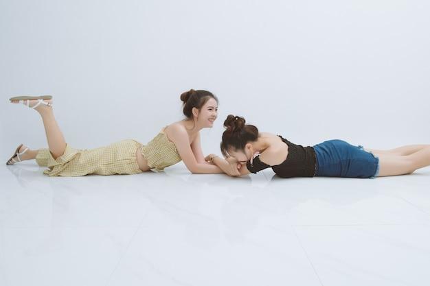 Portret dwóch kobiet szczęśliwy w studio; emocje, ludzie, nastolatki i pojęcie przyjaźni na białym tle. dwie kobiety azjatyckie śmiejąc się śmieszne.