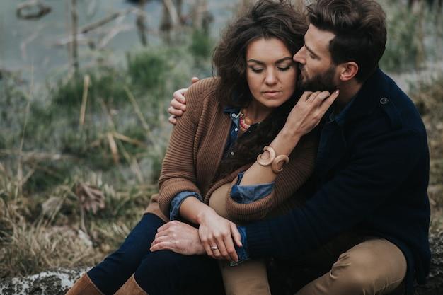 Portret dwóch kochanków kaukaski. młoda para przytulanie w jesienny dzień na świeżym powietrzu. brodaty mężczyzna i zakochana kędzierzawa kobieta. walentynki.