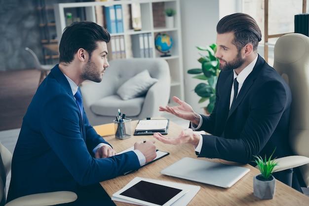 Portret dwóch ładnych atrakcyjnych przystojnych eleganckich modnych mężczyzn pracowników ekonomista finansista agent pośrednik omawiający strategię plan innowacji w jasnym białym wnętrzu miejsce pracy stacja w pomieszczeniu
