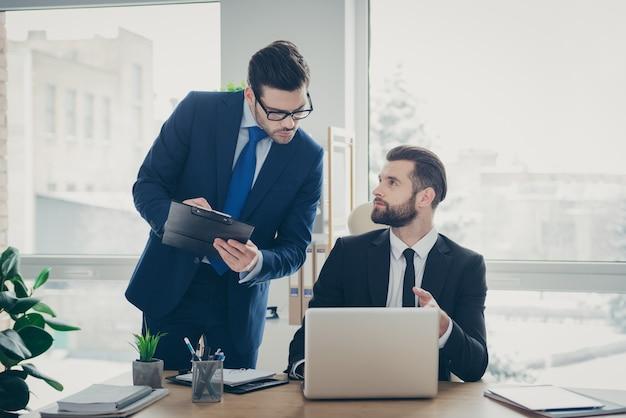Portret dwóch ładnych, atrakcyjnych, przystojnych, imponujących mężczyzn, ekonomista, finansista, agent agenta, omawiający rozwój tego pomysłu na start, wzrost pieniędzy w jasnym białym wnętrzu miejsca pracy