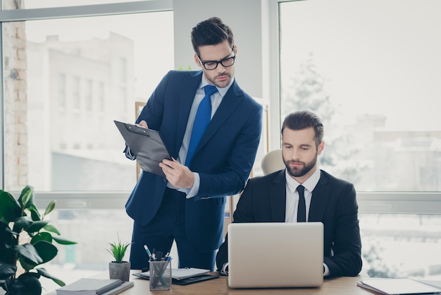 Portret dwóch ładnych, atrakcyjnych, przystojnych, inteligentnych, wykwalifikowanych mężczyzn, bankier, ekonomista, finansista, rozwijając go, rozpoczynając badanie danych rynkowych, w jasnym białym wnętrzu stacji roboczej