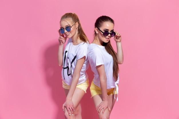 Portret dwóch ładnych dziewczyn najlepszych przyjaciół, pozowanie razem na różowej ścianie