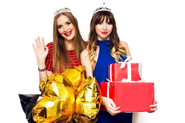Portret dwóch ładnych kobiet z jasnymi balonami i pudełkami na prezenty