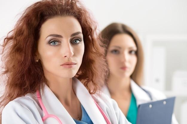 Portret dwóch lekarzy stojących w recepcji spotkania pacjentów i gotowych do pracy