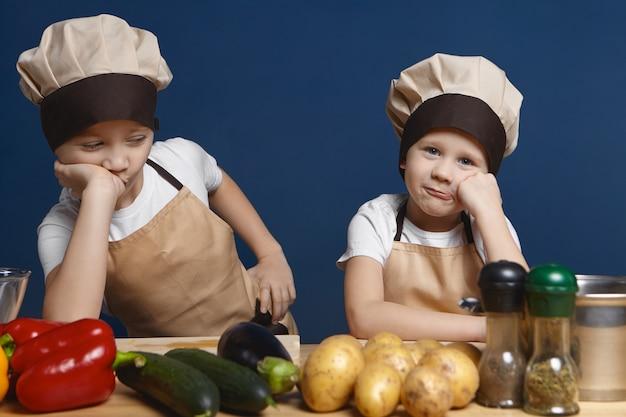 Portret dwóch małych chłopców ubranych w mundur szefa kuchni o znudzonym wyglądzie