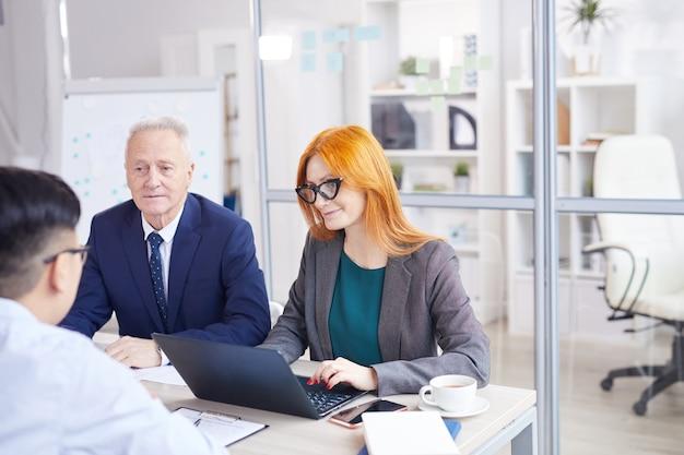 Portret dwóch menedżerów hr przeprowadzających rozmowy kwalifikacyjne z azjatyckim młodym człowiekiem na stanowisko w biurze, kopia przestrzeń
