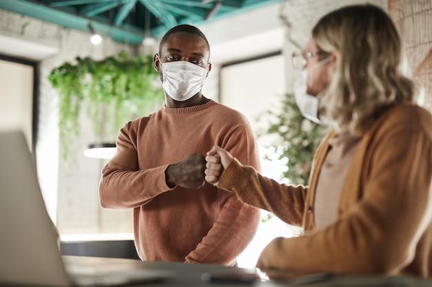 Portret dwóch mężczyzn noszących maski i uderzających pięściami podczas bezdotykowego powitania w kawiarni lub biurze, koncepcja covid