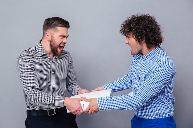 Portret dwóch mężczyzn walczących o folder na szarej ścianie