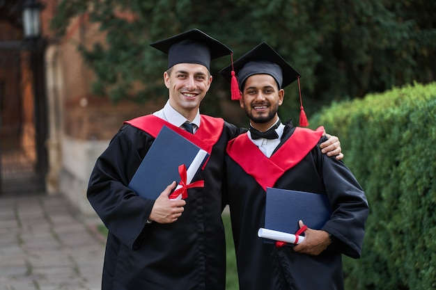 Portret dwóch międzynarodowych przyjaciół absolwentów w sukniach ukończenia szkoły z dyplomem w rękach.