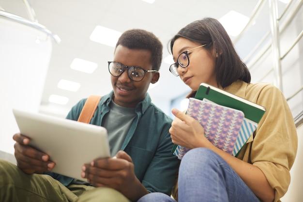 Portret dwóch międzynarodowych studentów czytających razem książki